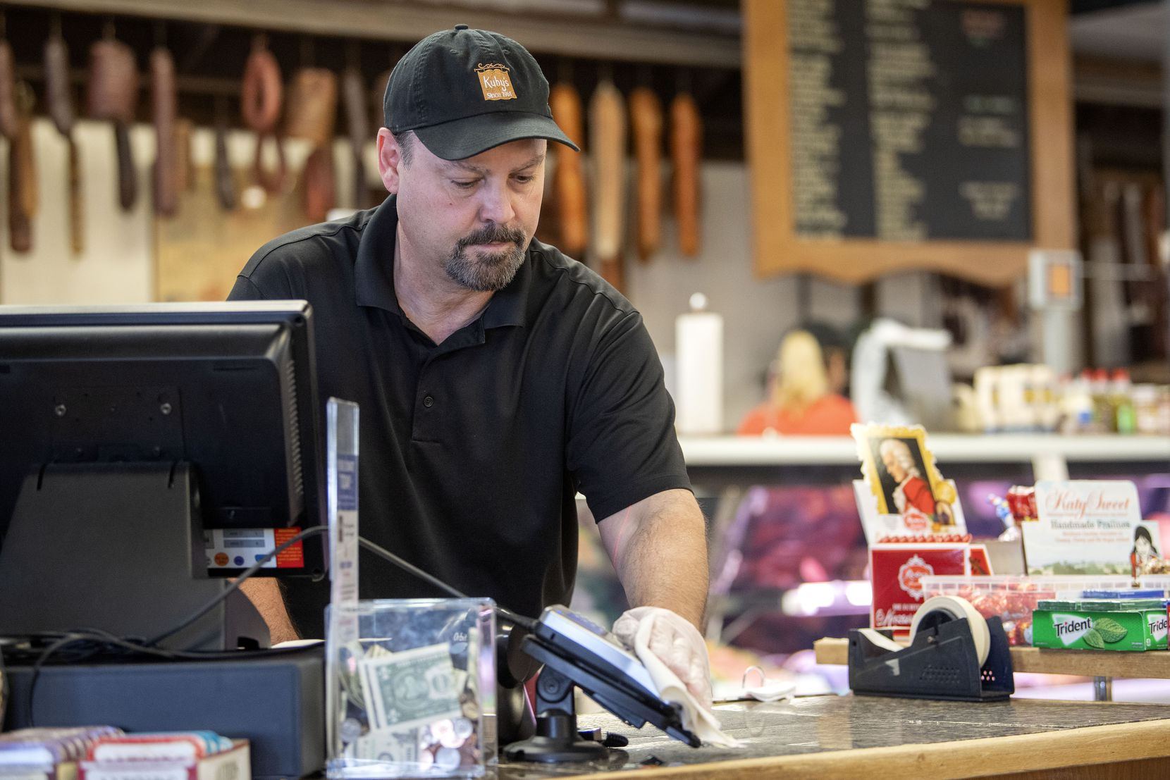 Karl Kuby Jr., owner of Kuby's Sausage House and European Market, sanitizes the credit card machine on Tuesday, March 24, 2020 in Dallas.