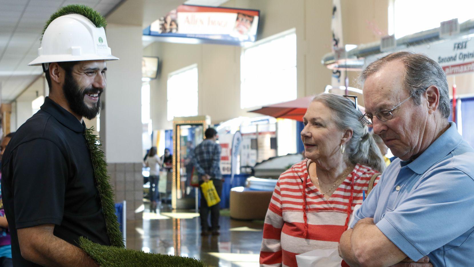 A couple talks to a representative from Synthetic Grass Pros during the Collin County Home & Garden Show in Allen.