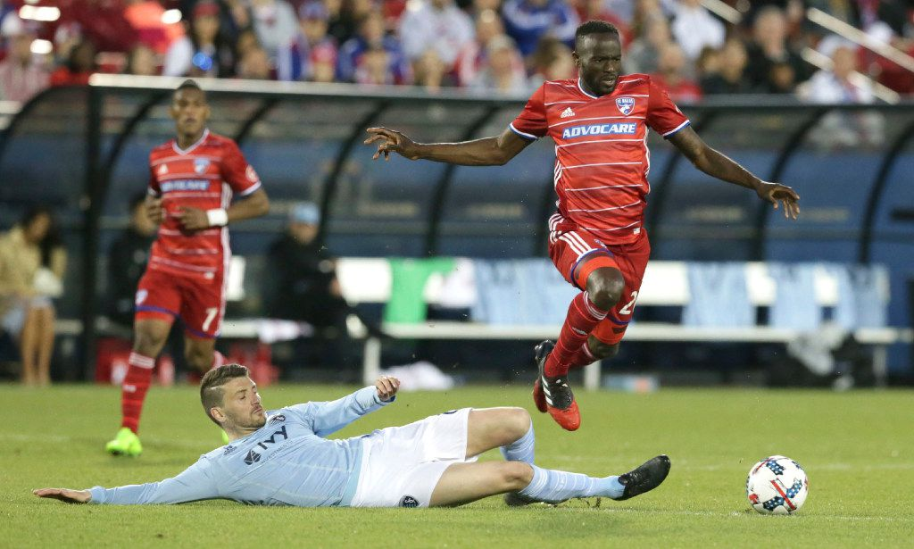 FC Dallas forward Roland Lamah, right, jumps over the tackle against Sporting Kansas City midfielder Ilie Sanchez (6) during the second half of an MLS soccer match in Frisco, Texas, Saturday, April 22, 2017. (AP Photo/LM Otero)