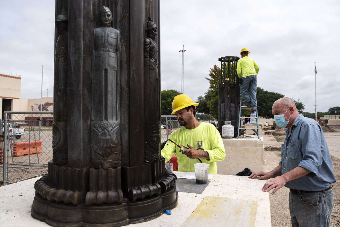 Michael Van Enter, right, watches a contractor working on one of the Torchiere lamps outside the main entrance to the Hall of State at Fair Park.