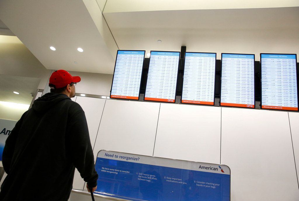 A man looks at the flight boards for an available flight out of DFW Airport on Wednesday evening. American Airlines stopped operations as severe storms were supposed to go through the DFW area on Wednesday,  April 17, 2019 DFW Airport.