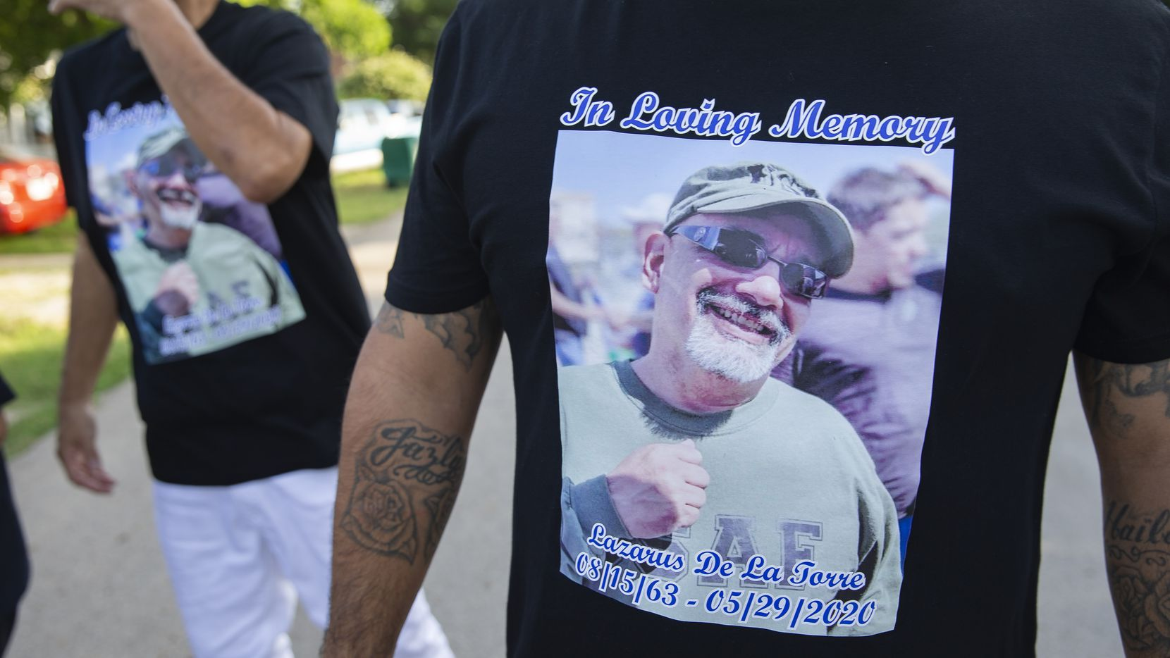 """Family members of the late Lazarus De La Torre wear T-shirts bearing one of their favorite images of """"Pastor Laz,"""" a photo taken while he was helping feed the homeless in downtown Dallas."""