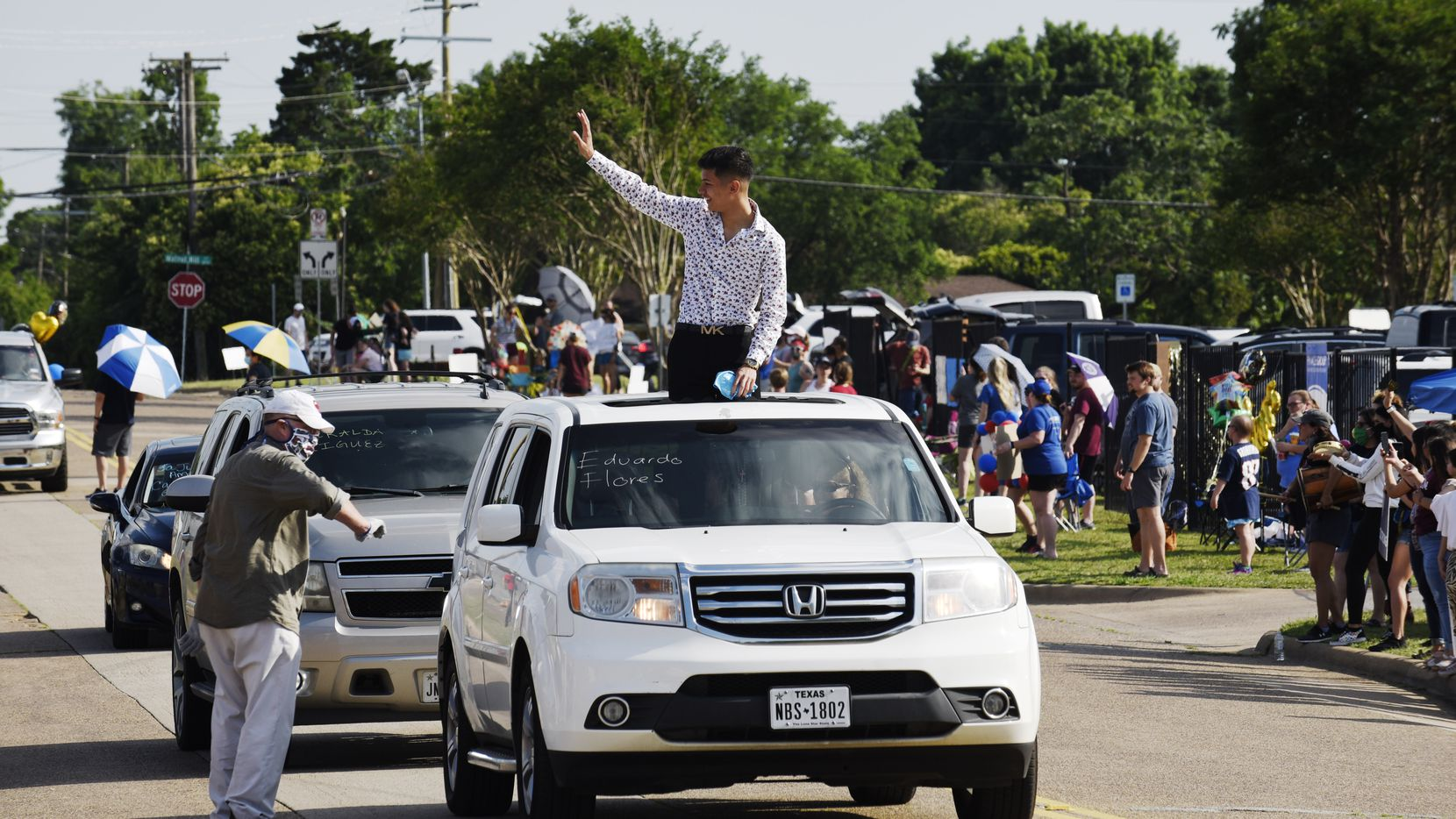 Senior Eduardo Flores, varsity soccer captain and president of the National Honor Society, waves to faculty and staff as his mom drives him through a senior parade outside of Thomas Jefferson high school in Dallas, Tuesday afternoon May 19, 2020. The event titled Senior Sunset, treated the graduating seniors to a parade while receiving personalized graduation signs and their cap and gown.
