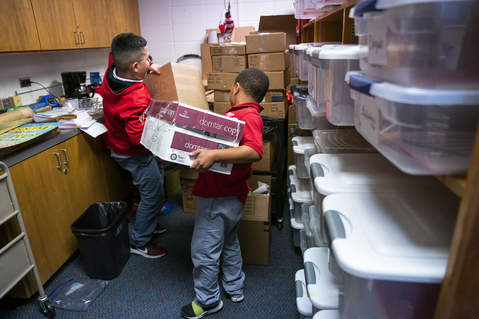 Students help moves boxes of books and supplies in the library at the new Walnut Hill Elementary. The district continues to work on a needs inventory to help determine how to spend the cash donations received since the Oct. 20 tornadoes.