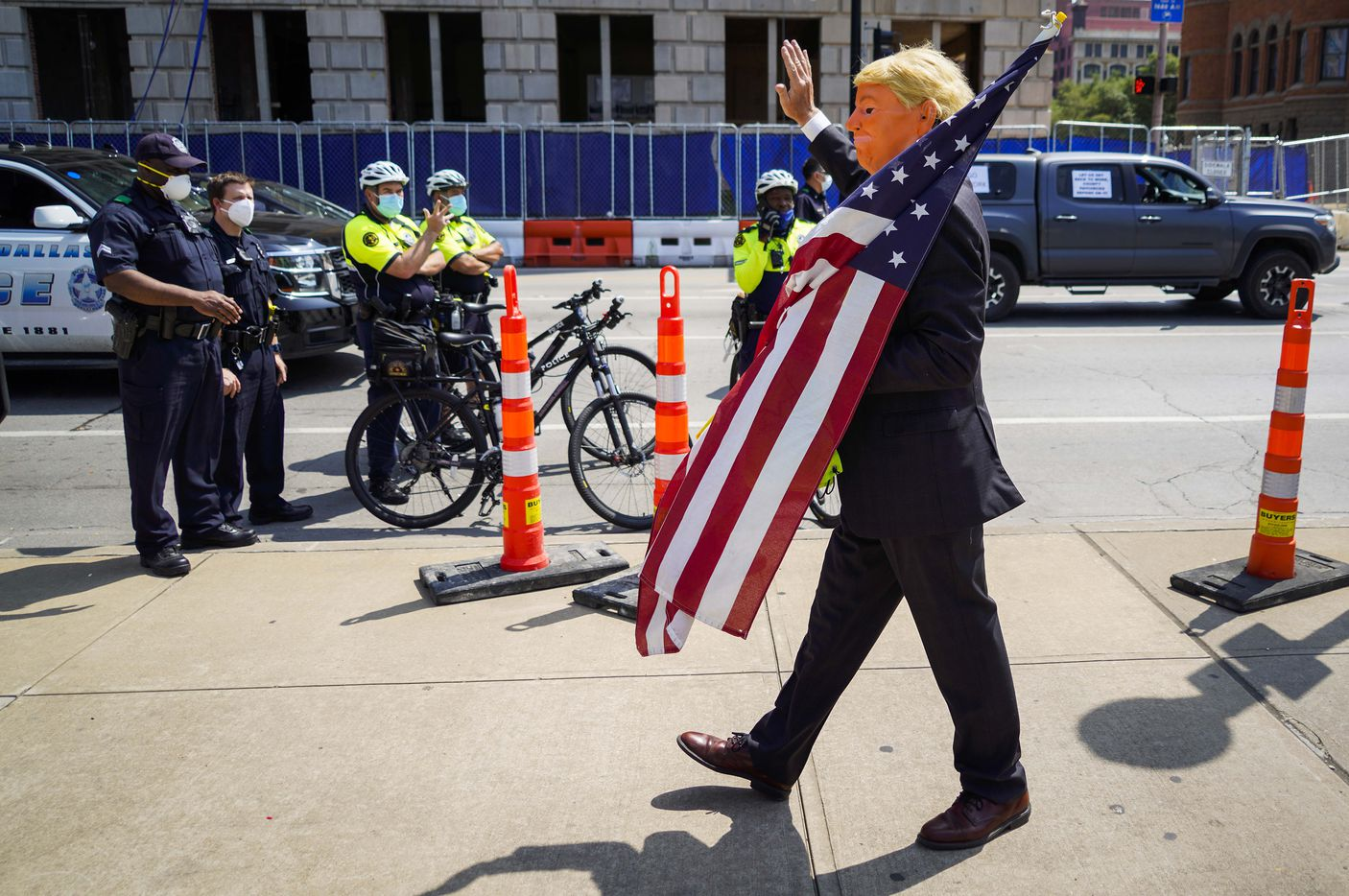 A protester wearing a mask of President Trump waves to Dallas police wearing face masks as rally against government stay-at-home orders at Dealey Plaza on Tuesday, April 21, 2020, in Dallas.
