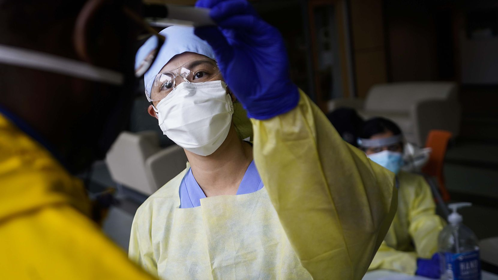 The state dental board imposed stiffer requirements on protective equipment in dentists' office late Thursday, just hours before Gov. Greg Abbott's orders postponing elective procedures because of coronavirus expire early Friday. Dallas dentist Jennifer Lo is shown screening a messenger at Northwest Community Center earlier this month.