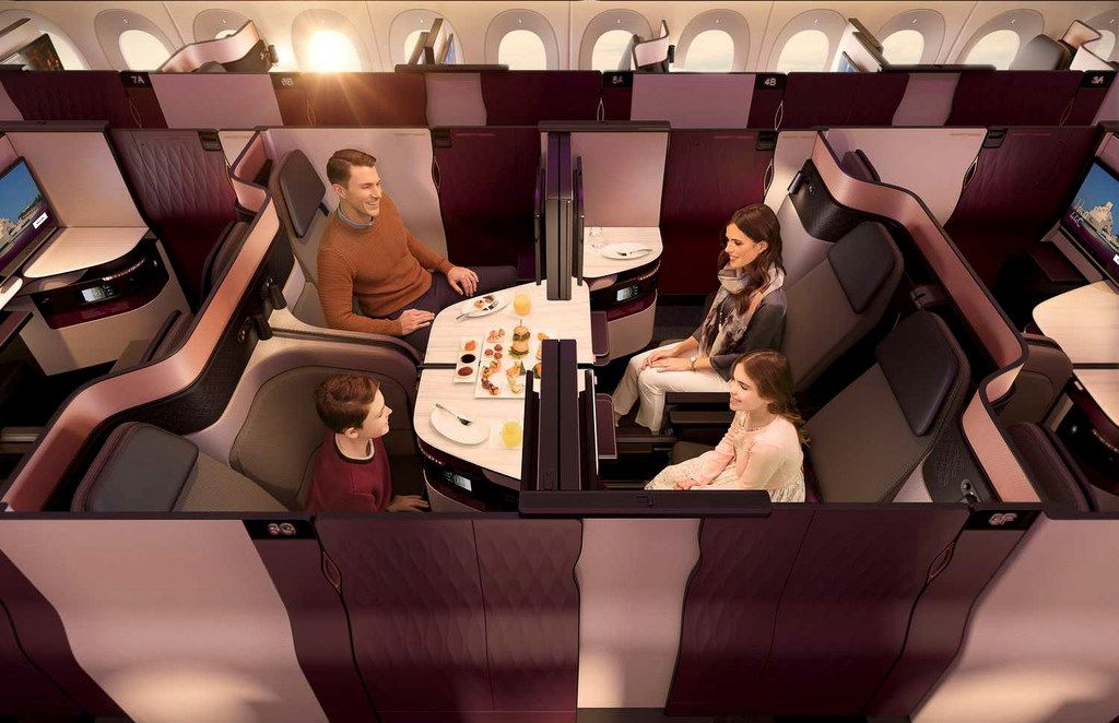 Four passengers traveling together can drop the interior partitions in the Qsuite middle section to accommodate family dining or a business conference.
