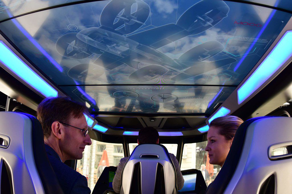 Visitors sit inside the Bell Nexus concept vehicle at the Uber Elevate Summit in Washington, D.C., one of the vertical takeoff and landing vehicles that will be part of Uber's fleet for aerial ride sharing.