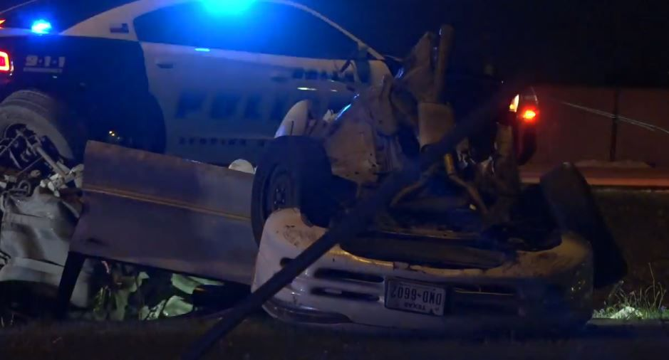 The remains of a car that collided with a light pole lay in front of a Dallas police squad car Thursday morning.