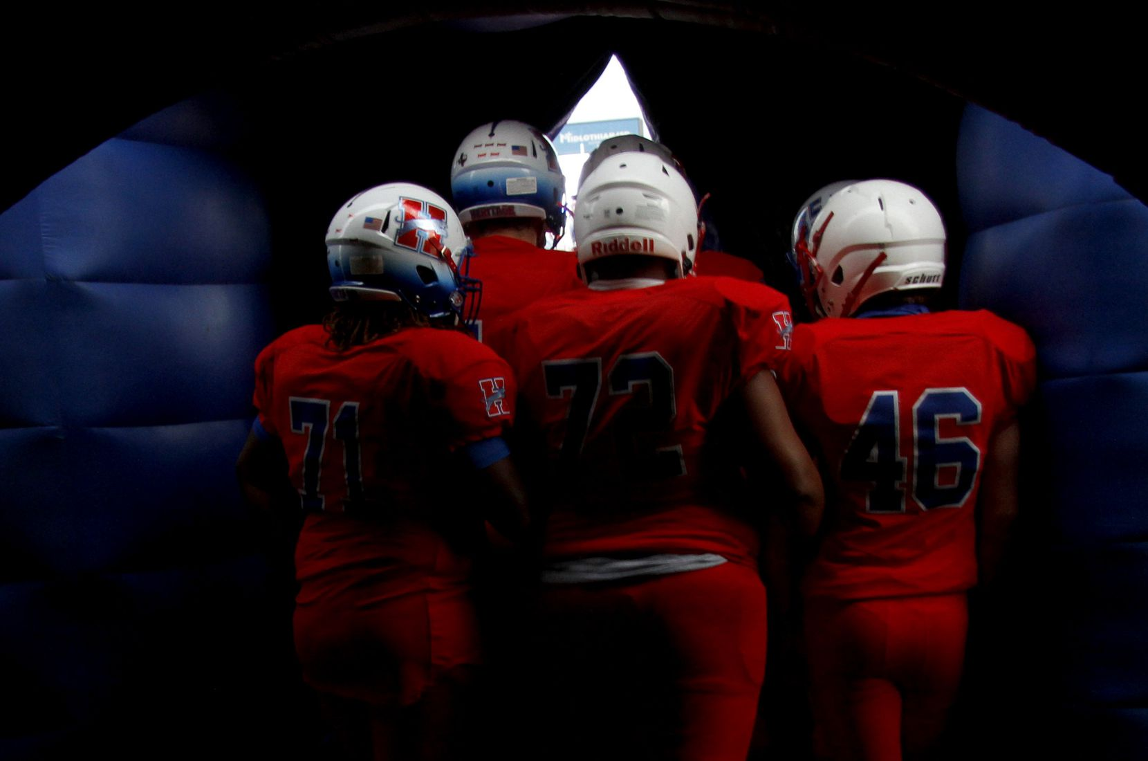 Midlothian Heritage players huddle and peek through an opening of their team inflatable prior to team announcements before the kickoff of their game against Lindale. The two teams played their Class 4A football game at Midlothian ISD Multipurpose Stadium in Midlothian on September 4, 2020. (Steve Hamm/ Special Contributor)