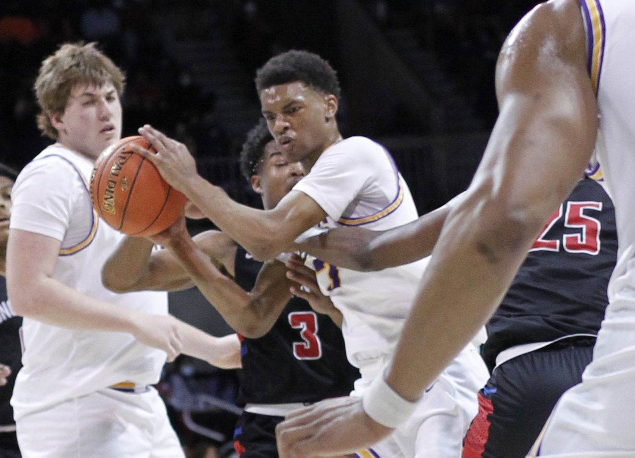 Richardson guard Rylan Griffen (3), center,  grimaces as he dribbles through congestion during first half action against Duncanville. Griffen was called for traveling on the play. The two teams played their Class 6A state semifinal boys basketball playoff game at Moody Coliseum on the campus of SMU in Dallas on March 9, 2021. (Steve Hamm/ Special Contributor)