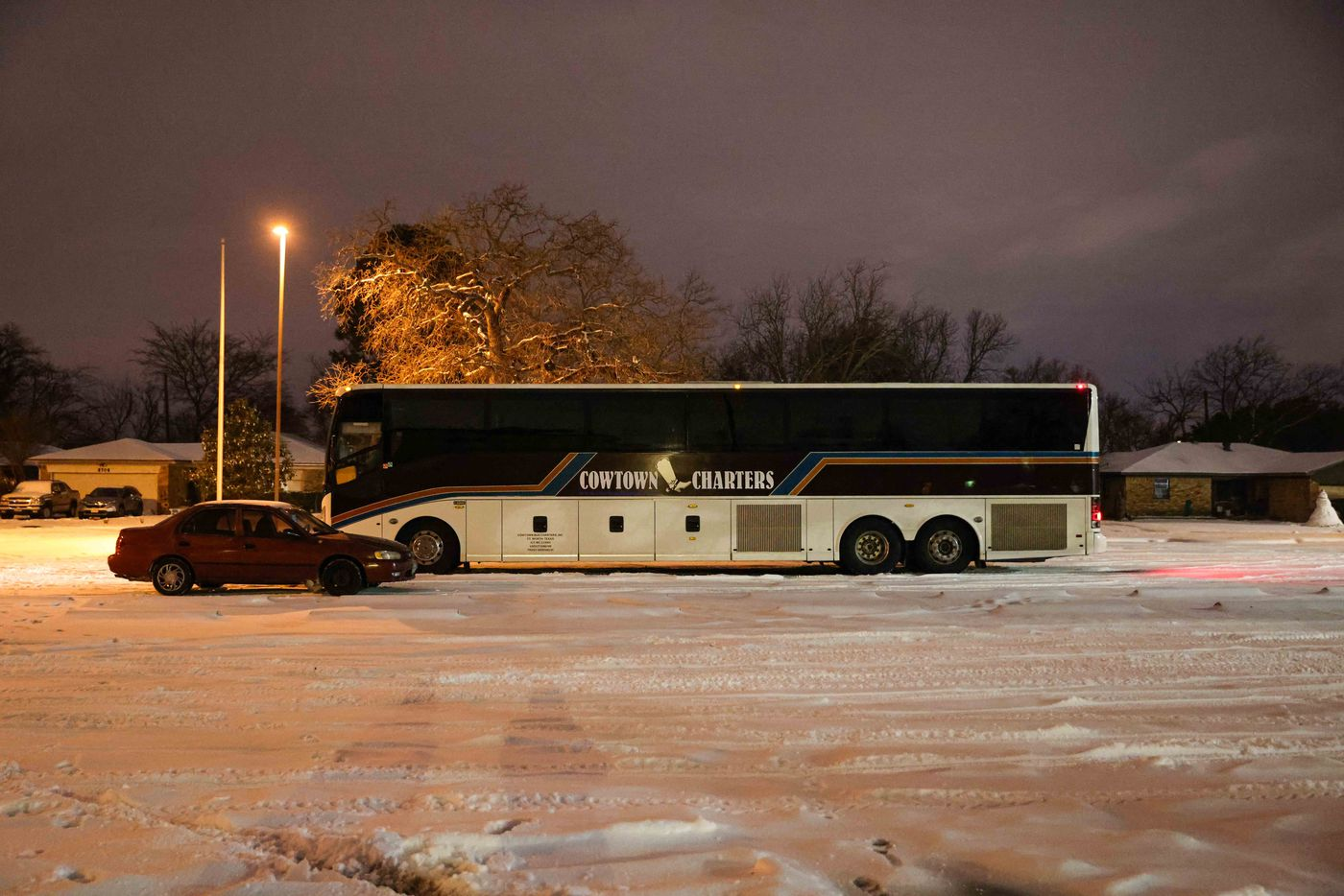 Marleny Almendarez's car is parked next to a charter bus that serves as a warming center for the Pleasant Groves community at Pleasant Oaks Recreation Center on Wednesday, February 18, 2021 in Dallas.