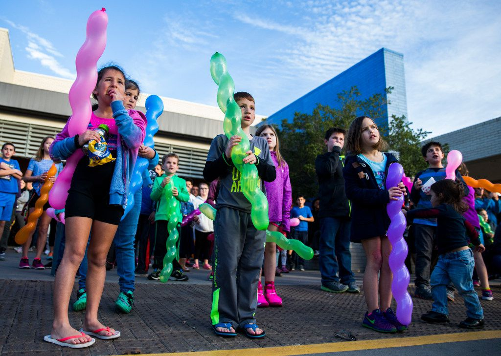 Children watch as a large outdoor menorah is lighted at the Aaron Family Jewish Community Center of Dallas.