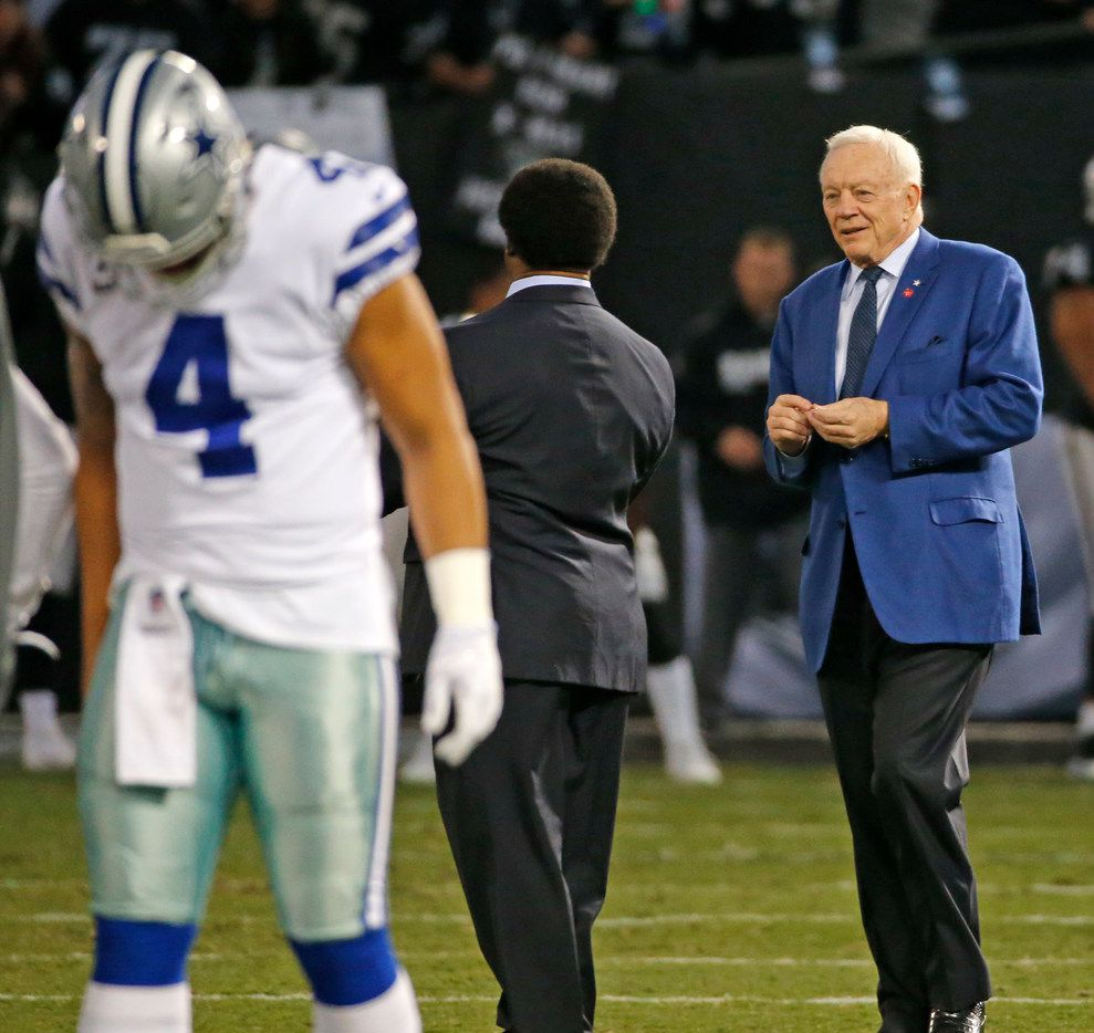 Dallas Cowboys owner Jerry Jones, right, is pictured on the field with Dallas Cowboys quarterback Dak Prescott (4) before the Dallas Cowboys vs. the Oakland Raiders NFL football game at the Oakland-Alameda County Stadium in Oakland, California on Sunday, December 17, 2017. (Louis DeLuca/The Dallas Morning News)