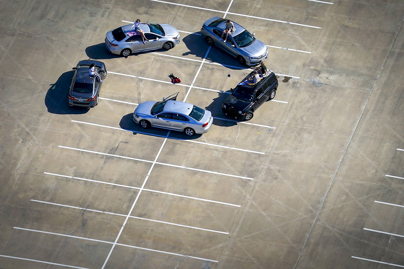 After the start of the pandemic, young people practiced social distancing while gathering in the parking lot at McKinney High School on March 24. Collin County instituted a stay-at-home order that took effect that day; Dallas County had put its order into place at 11:59 the previous night.