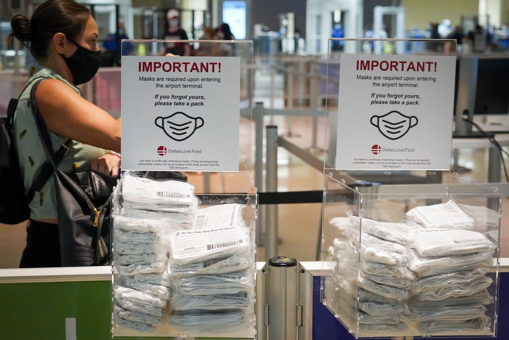 Una pasajera toma una bolsa con mascarillas de tela gratuitas que disponibles para viajeros en vuelos que parten del Aeropuerto Love Field de Dallas.