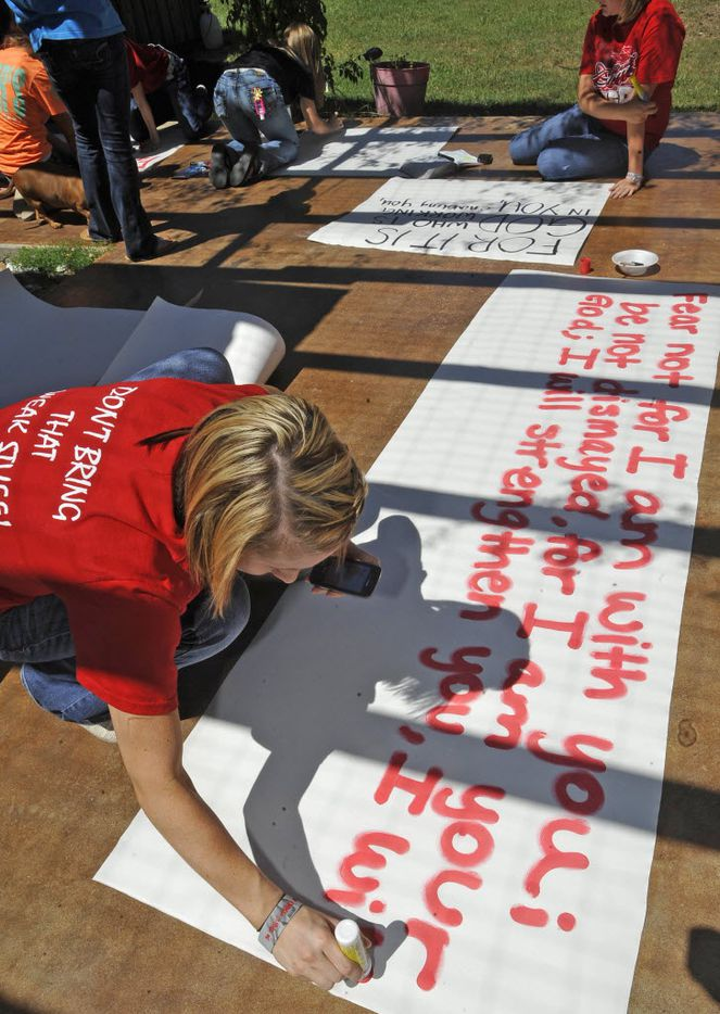 In this 2012 file photo, Brooke Coates, left, a cheerleader, paints a long sign on the patio.