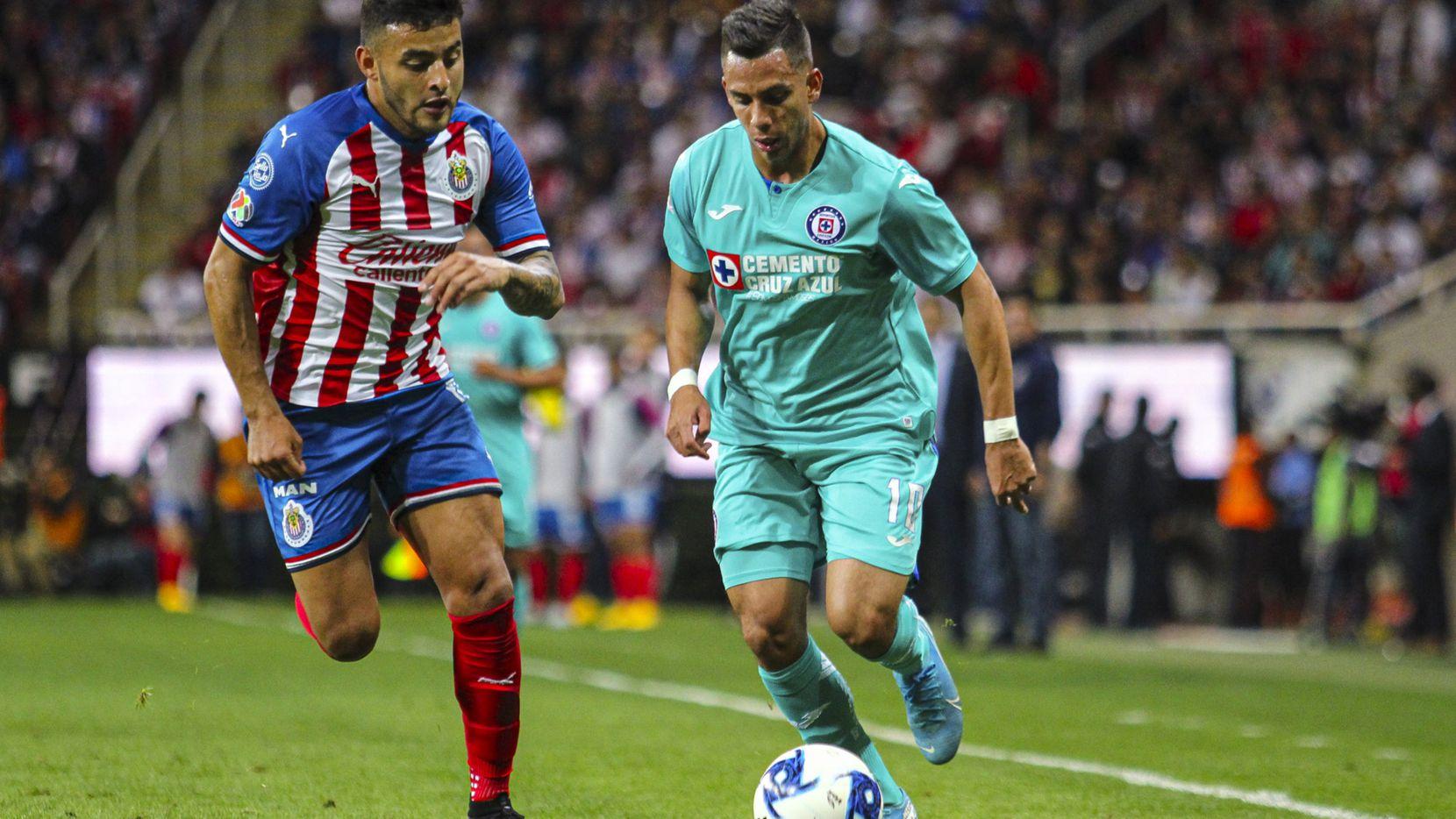 El delantero de Chivas, Alexis Vega (izq), pelea el balón con el jugador de Cruz Azul, Guillermo Fernández, en el juego disputado el 15 de febrero de 2020 en el Estadio Akron de Guadalajara.