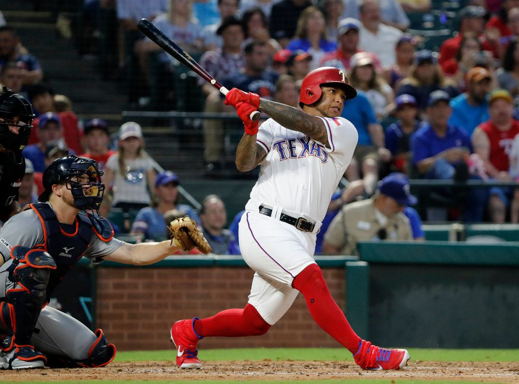 Texas Rangers' Willie Calhoun follows through on a solo home run as Detroit Tigers' Jake Rogers, left, watches during the fourth inning of a baseball game in Arlington, Texas, Saturday, Aug. 3, 2019. (AP Photo/Tony Gutierrez)