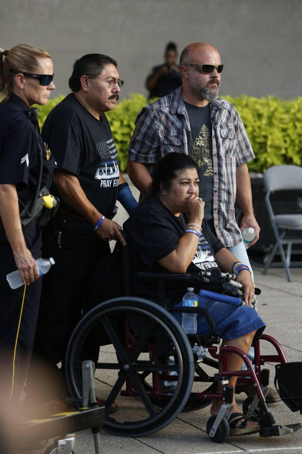 family members of the fallen police officers file in to a candlelight vigil hosted by the Dallas Police Association at Dallas City hall in Dallas, TX July 11, 2016. (Nathan Hunsinger/The Dallas Morning News)