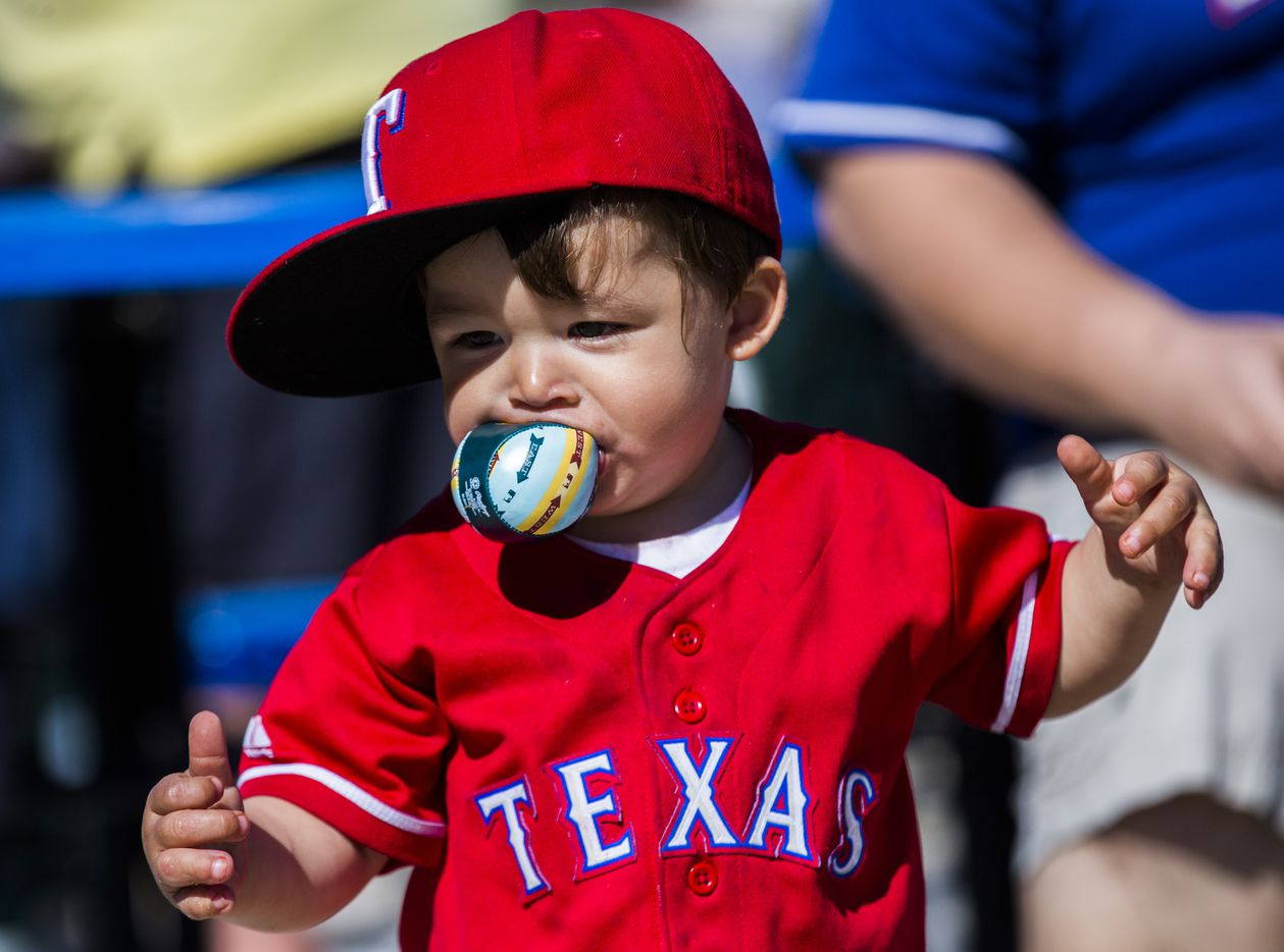Texas Rangers fan Victor Tena, 1, bites a plush baseball during a spring training game against the Kansas City Royals at the teams' training facility on Feb. 25 in Surprise, Ariz.