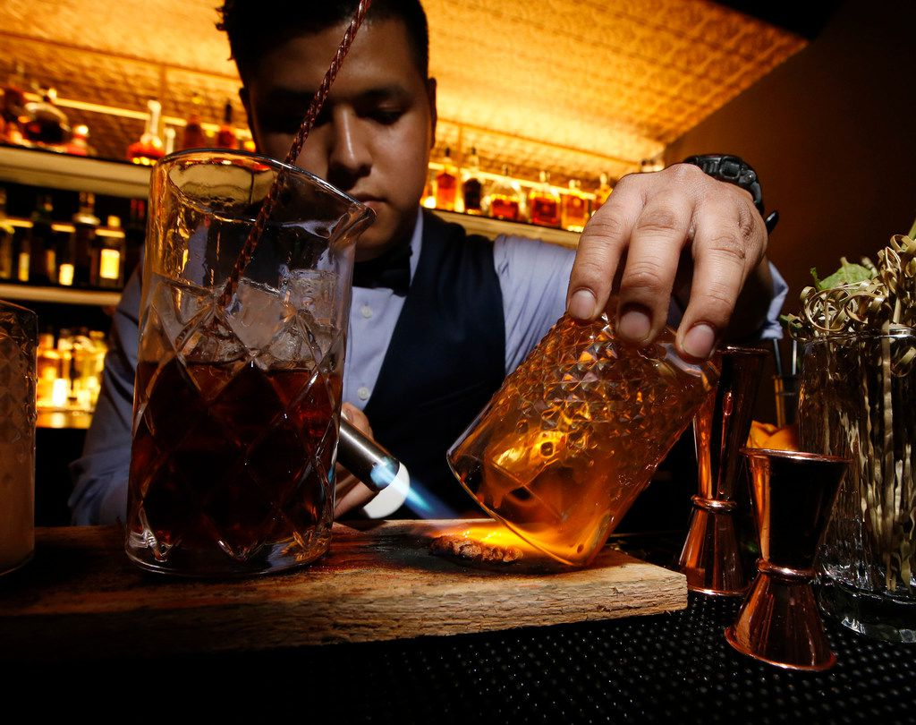 Cliff Felipe Flores makes a house smoked old fashion at ABV Establishment in Dallas on May 20, 2018.
