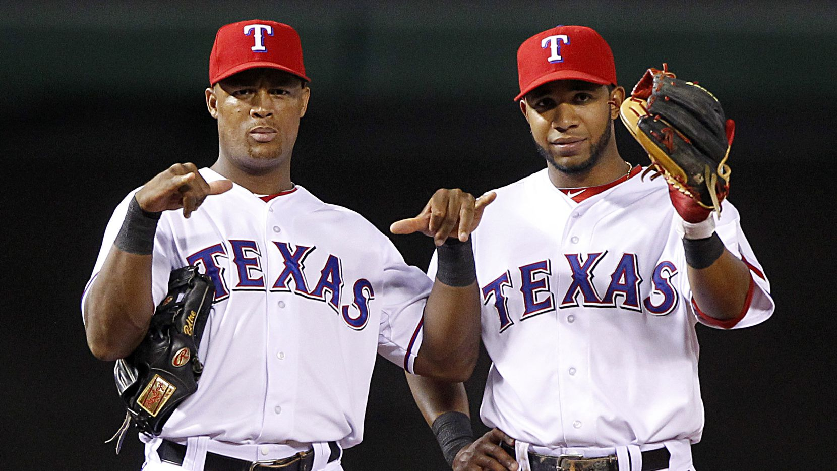 Texas Rangers third baseman Adrian Beltre, left, and shortstop Elvis Andrus (1) flash signals to the dugout during a break in the action agains the Oakland A's at the Rangers Ballpark in Arlington, Tuesday, May 21, 2013.