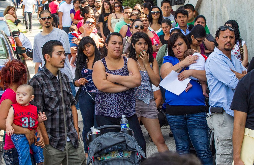 In this Aug. 15, 2012, file photo, a line of people living in the U.S. without legal permission wait outside the Coalition for Humane Immigrant Rights in Los Angeles. California is suing the Trump administration over its decision to add a question about citizenship to the 2020 U.S. Census. In announcing the lawsuit Tuesday, March 27, 2018, California Attorney General Xavier Becerra says adding such a question is a reckless decision that would violate the U.S. Constitution and cause a population undercount.