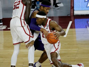 Oklahoma's De'Vion Harmon (11) goes against TCU's Kevin Easley Jr. (34) while Kur Kuath (52) sets a screen during the first half of an NCAA college basketball game in Norman, Okla., Tuesday, Jan. 12, 2021.