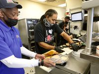 Dwight Harvey, left, and Kelan Williams package up hot food from Off the Bone Barbeque in Dallas on Tuesday, Feb. 23, 2021. Workers with the non-profit World Central Kitchen will hand out food at the Mattie Nash Myrtle Davis Recreation Center in Dallas starting at 1 p.m.