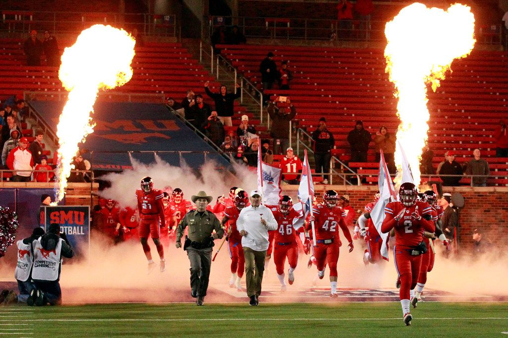 The SMU team enters the playing field through fire and smoke before the first half of a college football game between SMU and Tulsa at Ford Stadium in Dallas, Friday, October 27, 2017. (John F. Rhodes / Special Contributor)
