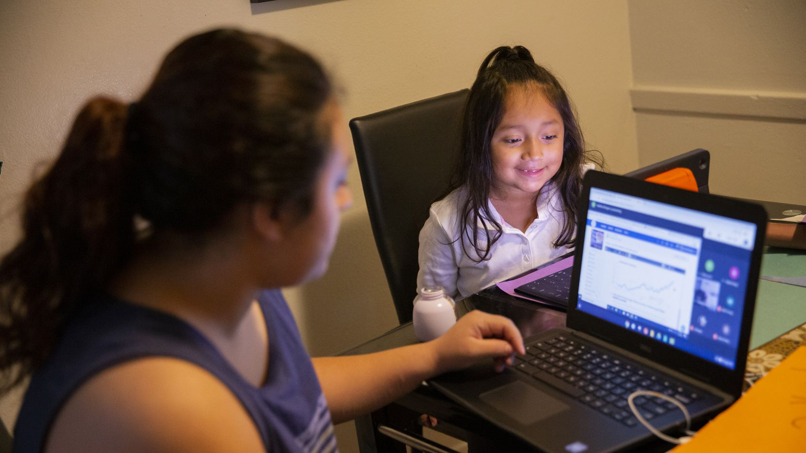 Hebreny Cojulum, 19, attends her integrated physics and chemistry class while sister Daysha Cojulum, 5, watches videos after her class at the kitchen table on Sept. 16, 2020 in Northwest Dallas. A little more than half of Dallas ISD families have said they will return to in-person learning when the district reopens campuses, according to recent survey results.