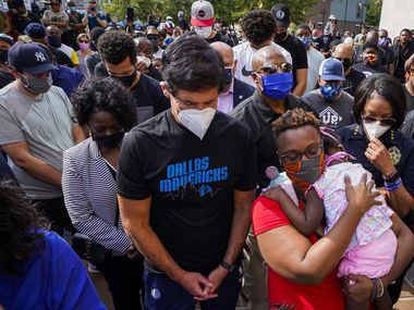 Dallas Mavericks owner Mark Cuban stands with Rev. Stacey Brown, who holds her daughter Tracey, 2, along with Dallas Police Chief Rene Hall (right) as they gather in prayer for a Dallas Prayer Gathering organized by Dallas clergy to pray For Justice & Against Racism at the Dallas Police Headquarters on Sunday, May 31, 2020, in Dallas. Behind Cuban are Dallas Mavericks players, from left, Jalen Brunson, Maxi Kleber, Justin Jackson and Dwight Powell.