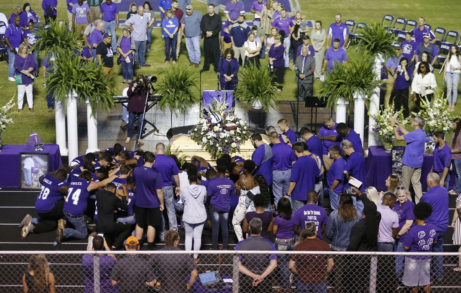 """Newton High School football team recites the Lord's prayer after a memorial service for Newton High School head football coach William Theodore """"W.T."""" Johnston at Curtis Barbay Field at Newton High School in Newton, Texas on Wednesday, May 15, 2019. (Vernon Bryant/The Dallas Morning News)"""
