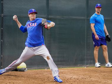 Texas Rangers pitcher Corey Kluber (right) watches teammate Kyle Gibson throw in the bullpen on the day pitchers and catchers reported for spring training at the team's training facility on Tuesday, Feb. 11, 2020, in Surprise, Ariz.
