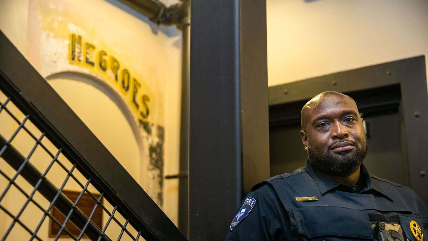 """Ellis County Constable Precinct 3 Curtis Polk Jr. poses for a photo at the Ellis County Courthouse in Waxahachie, Texas. His office was recently moved to a basement, where a segregation-era sign with the word """"negroes"""" is painted nearby."""