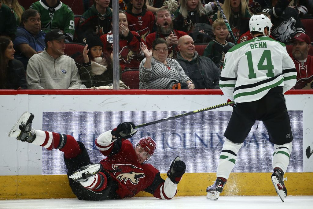 Dallas Stars left wing Jamie Benn (14) sends Arizona Coyotes left wing Lawson Crouse (67) to the ice on a check during the first period of an NHL hockey game Sunday, Dec. 29, 2019, in Glendale, Ariz.