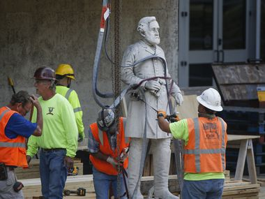 Construction workers move a statue of Robert E. Lee at Dallas' Pioneer Park on Monday.