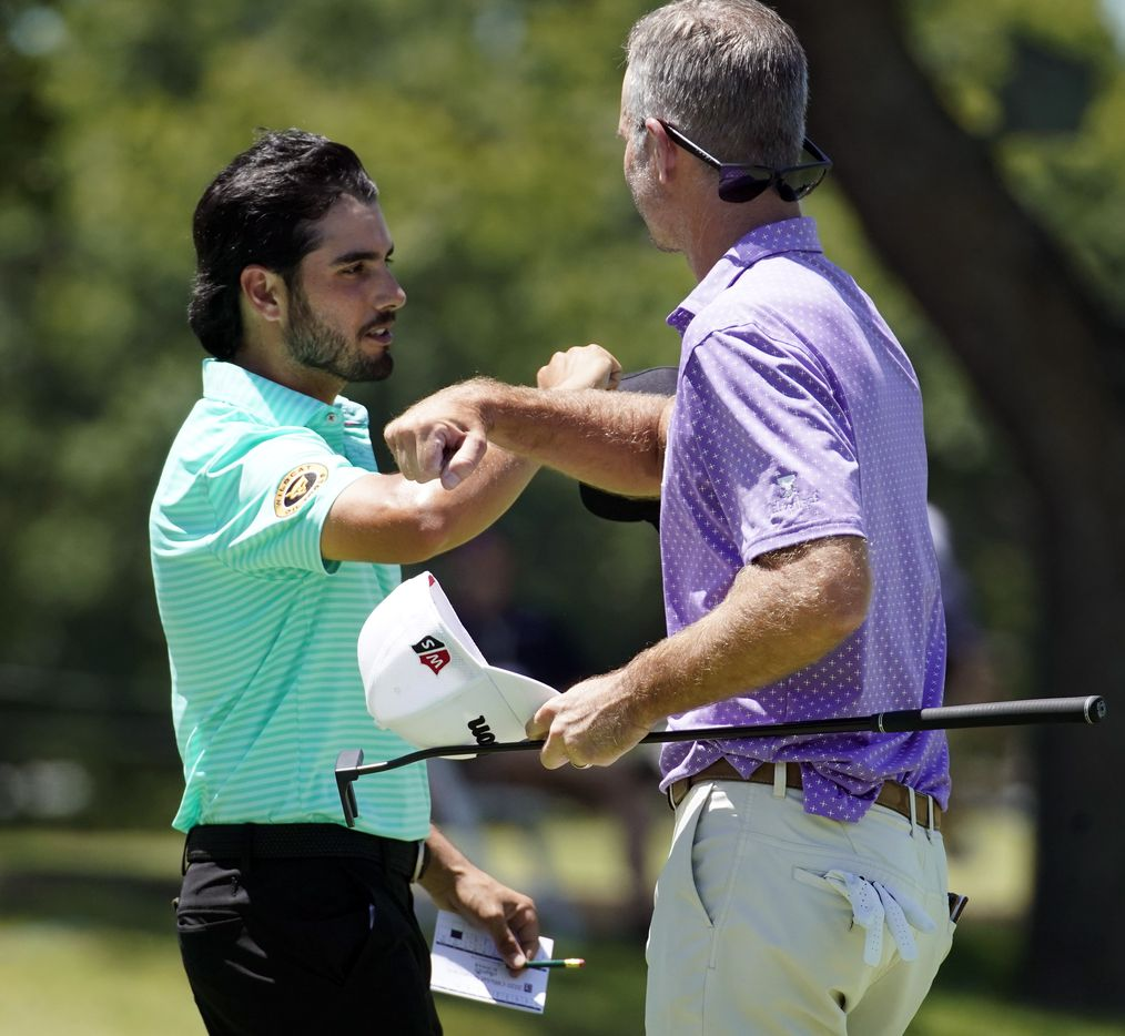 PGA Tour golfers Abraham Ancer (left) and Kevin Streelman bump elbows after finishing their opening round of the Charles Schwab Challenge at the Colonial Country Club in Fort Worth, Thursday, June 11, 2020.  The Challenge is the first tour event since the COVID-19 pandemic began. (Tom Fox/The Dallas Morning News)