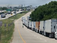 A long line of delivery trucks waits to enter the Amazon Fulfillment Center in South Dallas on Thursday.