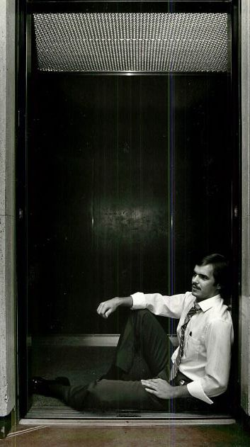 Greg Lee, an employee of Republic National Bank, sits by one of the elevator shafts to keep cool. According to Lee, this was the only place to keep cool since the power was shut off.  Photograph published in The Dallas Morning News on July 7, 1981.