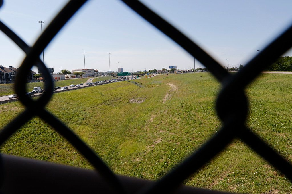 The chain link fence of a pedestrian bridge over LBJ Freeway frames undeveloped land on the north side of the freeway near Skillman Street on April 20, 2018.  The pedestrian bridge connects the south side of the freeway to the DART  LBJ/Skillman station. (Ron Baselice/The Dallas Morning News)