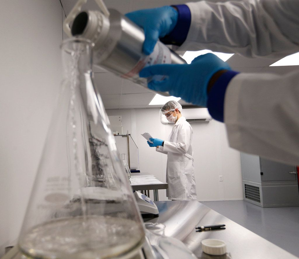 Product manager David Stermer (center) works on making terpenes as project manager Darius Bonds (pouring) works on making super lemon haze terpene at Ricca Chemical in Arlington. Ricca Chemical manufactures terpenes, organic chemical compounds that can be added to cannabis oil for aroma and flavor.