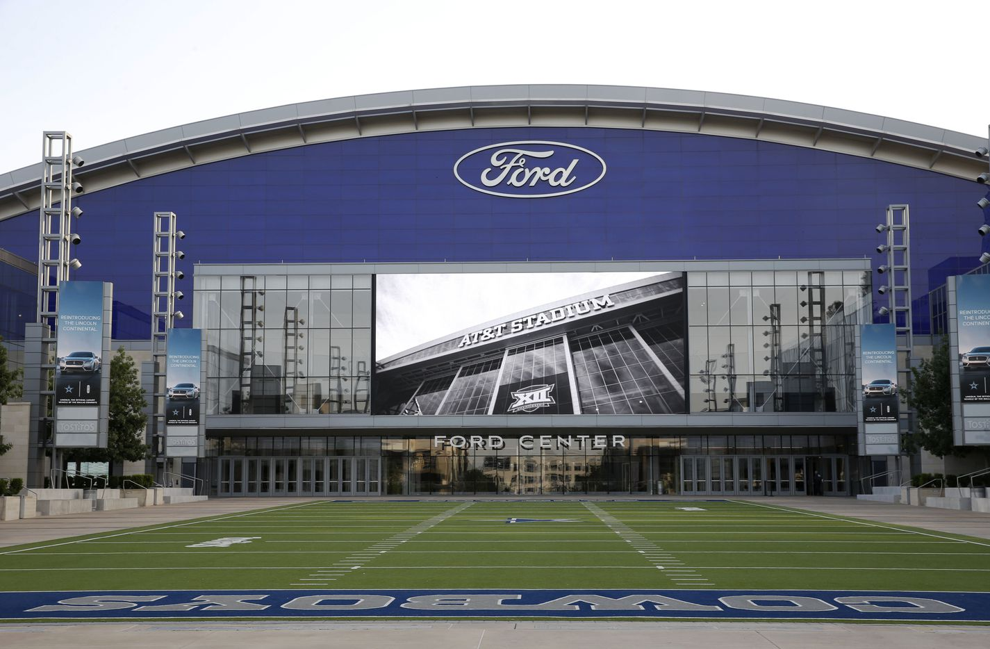 The Ford Center at The Star in Frisco on July 17, 2018. Various videos are shown on the big screen over the field. In this photo the screen shows an image of AT&T Stadium in Arlington, where the Cowboys play their games. The outdoor field is part of Tostitos Championship Plaza (foreground).