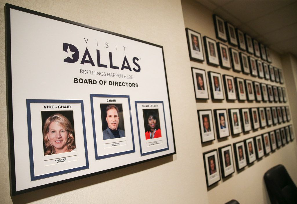 Photos of the VisitDallas Board of Directors fill a conference room wall at its downtown headquarters.