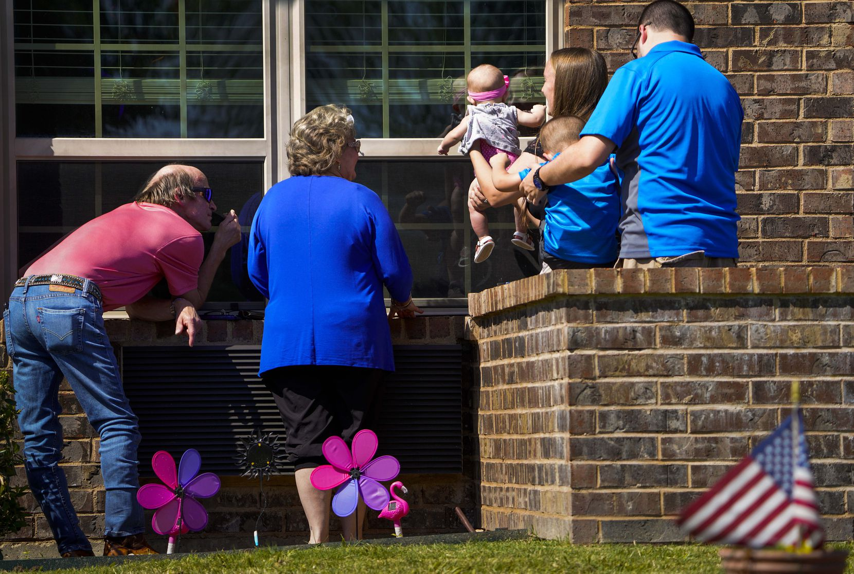 Meagan Myers held her 5-month-old daughter, Callie, up to the window of the baby's great-grandmother Peggy White on Mother's Day at The Pavilion at Creekwood, a health care and rehabilitation center in Mansfield, due to COVID-19 precautions on May 10, 2020. White had a stroke in late January and is due to be released from the facility at the end of May. Four generations of her family were present as her children, grandchildren and great-grandchildren visited her from outside the window. From left are, Randy White, Cindy Goleman, Meagan Myers, Chase Myers and Robert Myers.