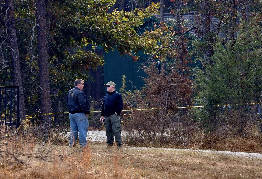 Law enforcement personnel stand near police tape on Todd Kohlhepp's property in Woodruff, S.C. Sunday, Nov. 6, 2016. A wooden storage shed is seen in the background. A woman was found earlier this week in a locked metal container on Kohlhepp's property in rural Woodruff. Kohlhepp is due in court for a bond hearing Sunday after investigators say he confessed to an unsolved quadruple murder that happened 13 years ago. He's also charged with the woman's kidnapping, and prosecutors say more charges are expected. (AP Photo/Richard Shiro)