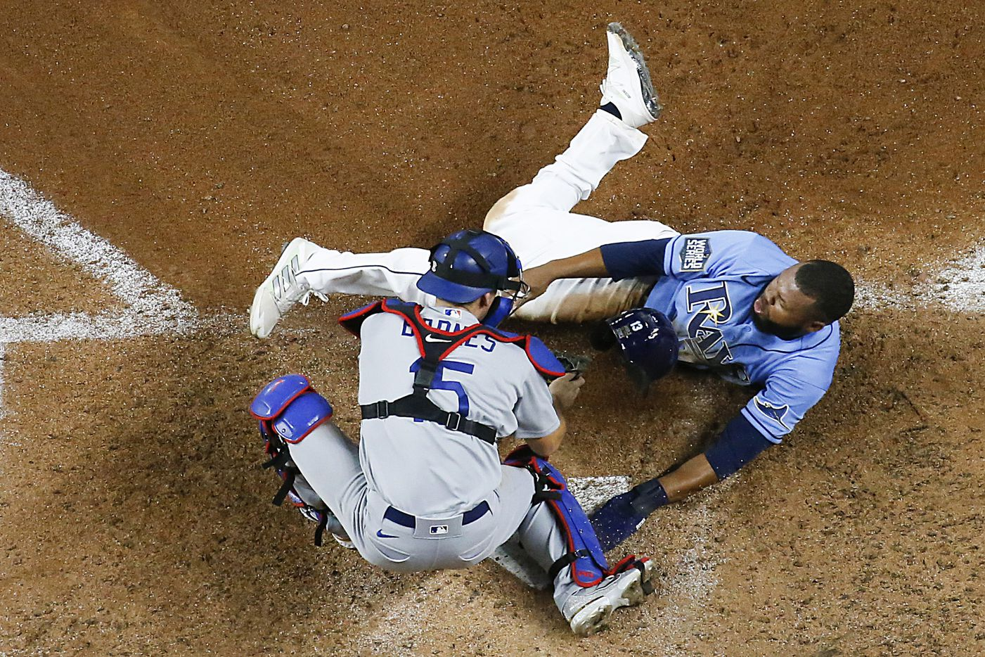 Tampa Bay Rays right fielder Manuel Margot (13) is tagged out by Los Angeles Dodgers catcher Austin Barnes (15) who was caught trying to steal home during the fourth inning of game five of the World Series at Globe Life Field on Sunday, October 25, 2020 in Arlington, Texas.