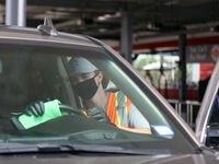 Los empleados de Tommy Terrific's Car Wash en Plano usan desinfectantes y mascarillas mientras realizan la limpieza al detalle de los vehículos.