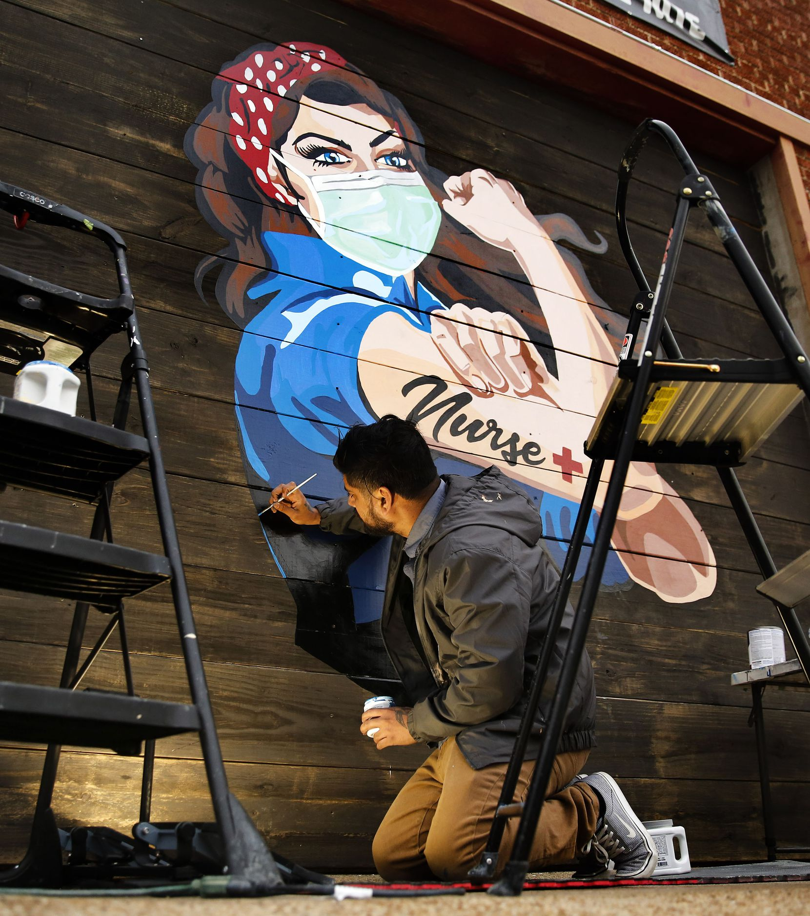 Dallas Artist Miguel Barajas paints a mural of a nurse on the exterior of Redfield's Tavern near Parkland Memorial Hospital, Thursday, April 2, 2020. The hospital is currently pursuing lawsuits against some of its former nurses for breaching their employment contracts by quitting early.